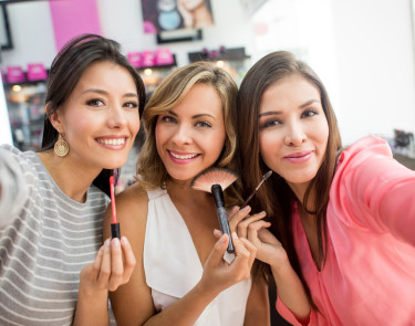 Friends taking a selfie while applying makeup